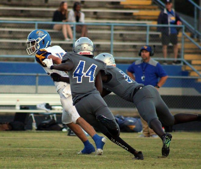 First Coast pass rushers Devion Hill (44) and Lonell McCall (31) pursue Fernandina Beach quarterback Chris Turner during Friday's high school spring football.