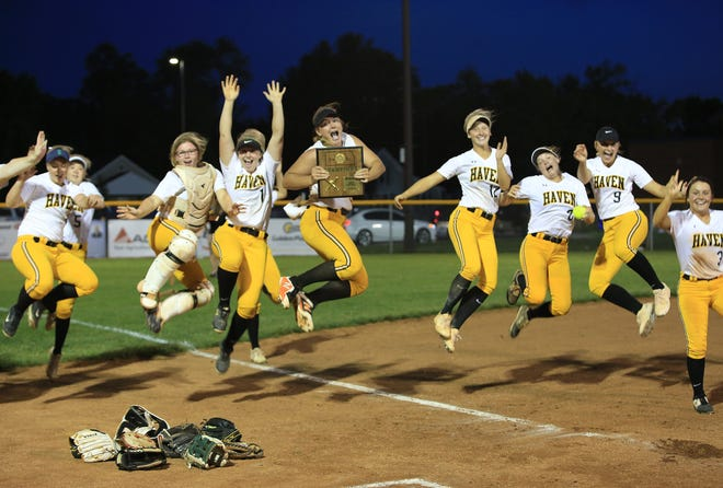 The Haven softball team jumps in the air with their Class 3A regional softball championship trophy Friday night in Hesston after defeating Smoky Valley 8-3.