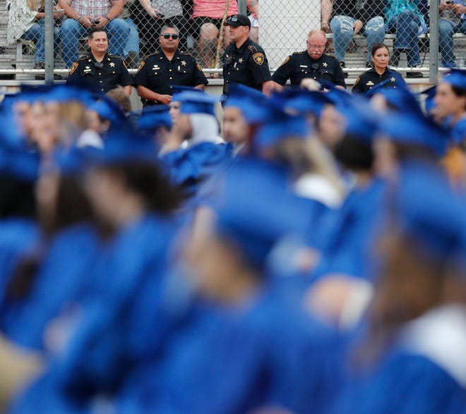 Lubbock Sheriffs Office officers watch as J.D.Harvey receives his diploma. Harvey's dad, deputy Cpl. D. Robert Harvey was killed in the line of duty in 2009 by a drunk driver. Frenship High School held their class of 2021 Friday, May 22, 2021 at Peoples Bank Stadium.