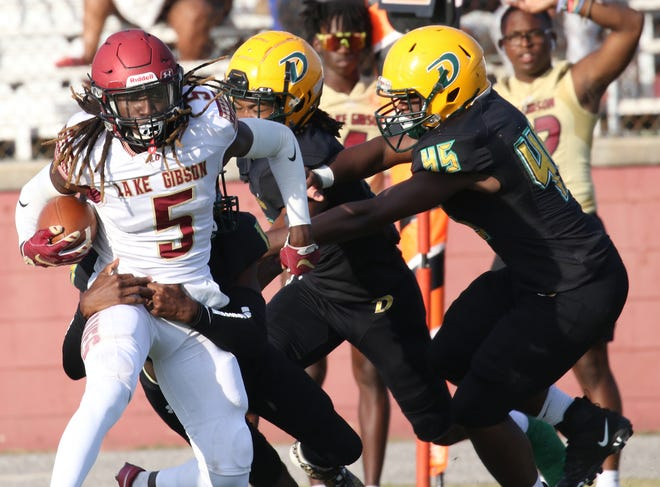 Lake Gibson wide receiver Sam McCall is tackled by DeLand defensive players after a short gain.