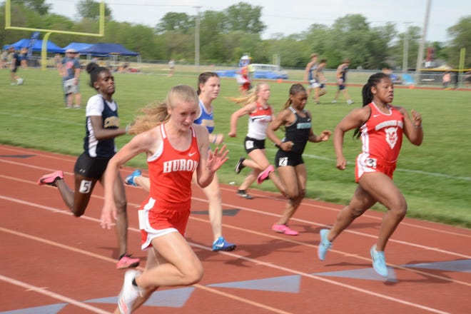 New Boston Huron's Elizabeth Anderson (foreground) won the girls 100 meters during the Division 2 Regional at Milan Friday.