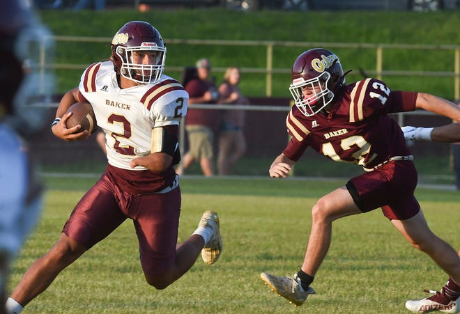 Kayleb Wagner runs the ball with Avery Stewart on his heels during a scrimmage Friday night in Baker.