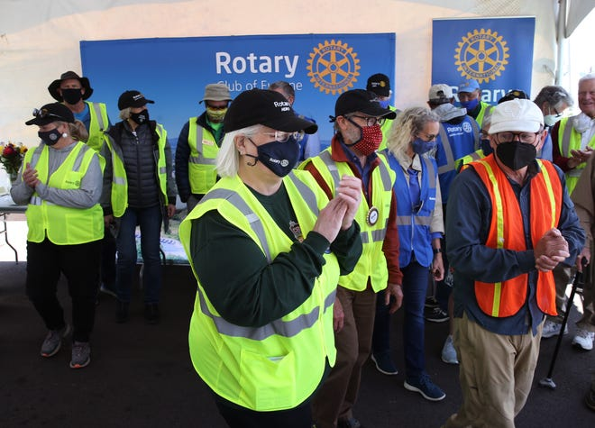 Rotary volunteer organizer Liz Nell, center, and fellow Rotarians celebrate together on the last day working at a drive through vaccination clinic at the Lane County Fairgrounds parking lot.  Members of the Rotary have been helping to get people vaccinated since early this year.
