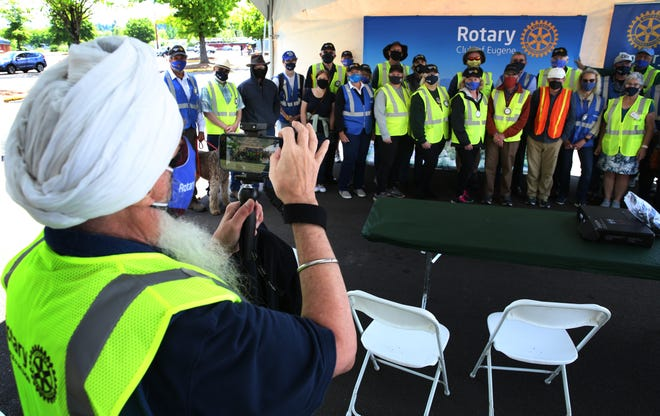 Rotarian Ravitej Khalsa, left, takes a group picture of fellow Rotary volunteers at the end of their last shift of helping at the Lane County popup vaccination clinic in the Lane County Fairgrounds parking lot.