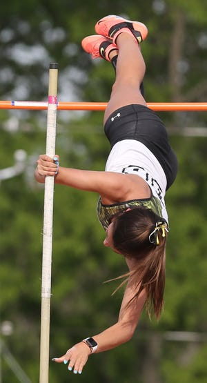 Perry's Kendal Fisher sets a Division I district meet record in the girls pole vault with a jump of 13 feet, 2 inches last week.