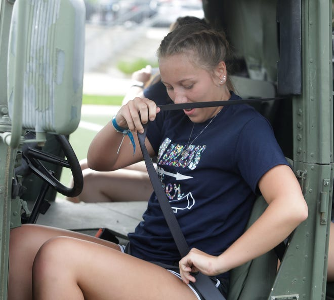 Fairless senior cheerleader Bry Fisk buckles herself in an Ohio Army National Guard Humvee during the 17th Annual Seat Belt Challenge held Saturday outside the Pro Football Hall of Fame in Canton.