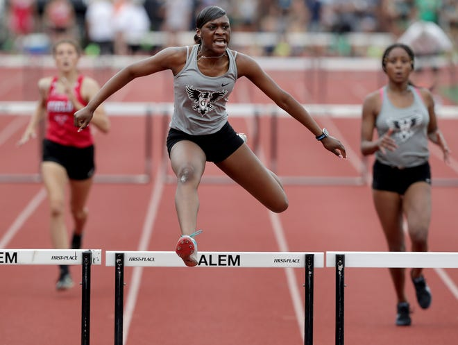 Buchtel junior DaMya Barker, center, clears a hurdle Saturday in the Division II district track and field meet at Salem High School. Barker finished first in four events with four meet record times.