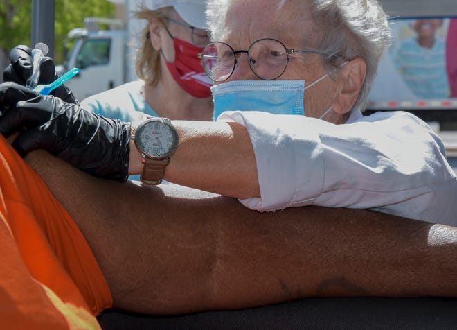 Dr. Milena Henzlova gives Earl McCullum of Sarasota a COVID-19 vaccination on Saturday morning during the All Faiths Food distribution in the Van Wezel parking area.