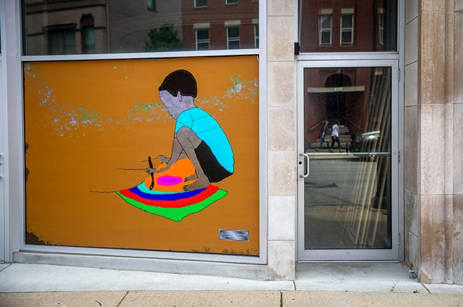 An art piece by Brooklynn Troemper of Springfield High School on display in the window of a building along Monroe Street as a part of the new Downtown Springfield Inc. ARTificiation installation with the Springfield High School art program, and Strong Springfield.