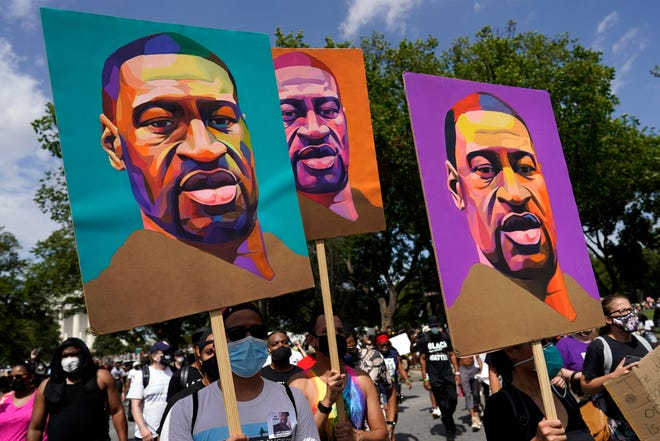 In this Aug. 28, 2020, photo, people carry posters with George Floyd on them as they march from the Lincoln Memorial to the Martin Luther King Jr. Memorial in Washington. On May 25, 2020, Floyd, a Black man, died when a white Minneapolis police officer pressed his knee on Floyd's neck for about 9 1/2 minutes while Floyd was handcuffed and pleading that he couldn't breathe.