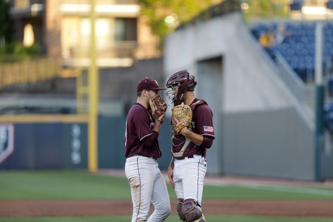 Benedictine's Carter Holton (19) talks with Cody Cowan (24) during a GHSA Class 4A state baseball championship game against Marist at Coolray Field in Lawrenceville on Thursday, May 20, 2021.