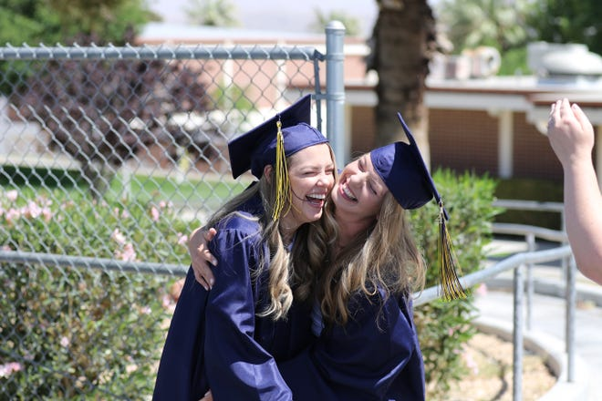 Two Barstow Community College graduates hug during a drive-thru event at the campus on May 14, 2021.