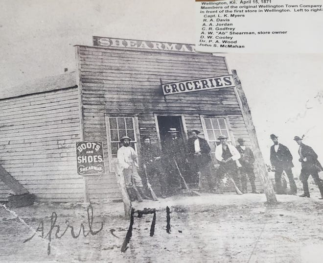 Members of the original Wellington Town Company in front of the first store in Wellington