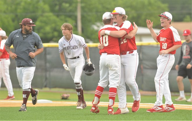 Albany's Zane Waggoner (22) celebrates with pitcher Jackson Chapman (10) as Tyler Chapman (20) looks on after the Lions got the final out to beat Hawley 6-2 on Saturday at Abilene High's Blackburn Field.