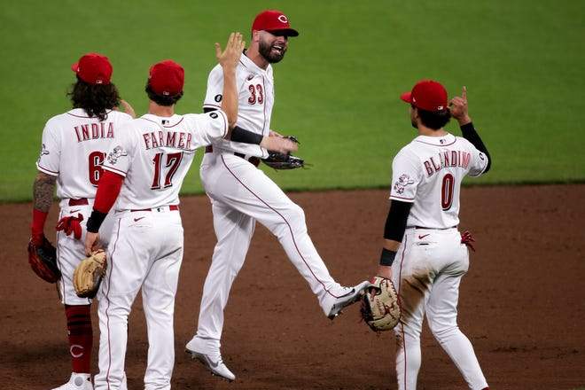 Cincinnati Reds left fielder Jesse Winker (33) high fives teammates at the conclusion of a baseball game against the Milwaukee Brewers, Friday, May 21, 2021, at Great American Ball Park in Cincinnati. The Cincinnati Reds won, 9-4.