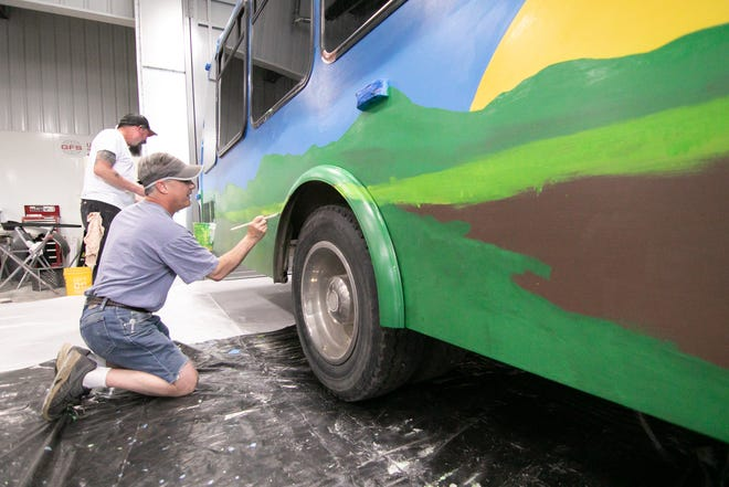 Stacy Karnes, left, and Michael Monroe paint a mural on a bus Raw Art is converting in a maker space for the Howell Nature Center, Saturday, May 22, 2021.