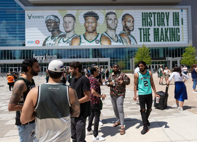 People mingle before the first-round playoff game between the Milwaukee Bucks and Miami Heat o Saturday, May 22, 2021, in the Deer District outside  Fiserv Forum in Milwaukee.
