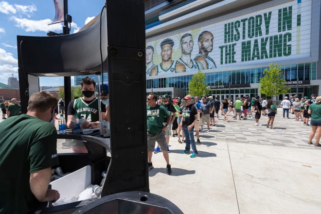 People wait in line for cold drinks before the first round playoff game between  the Milwaukee Bucks and Miami Heat Saturday, May 22, 2021 in the Deer District outside  Fiserv Forum in Milwaukee, Wis.