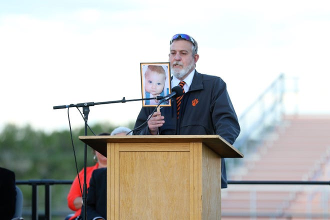 Aztec High School History Teacher and Wrestling Coach Monte Maxwell holds up a baby photo of his daughter Jocelyn Maxwell as he introduces her as Salutatorian on May 21 during the 2021 commencement ceremony at Fred Cook Memorial Stadium.