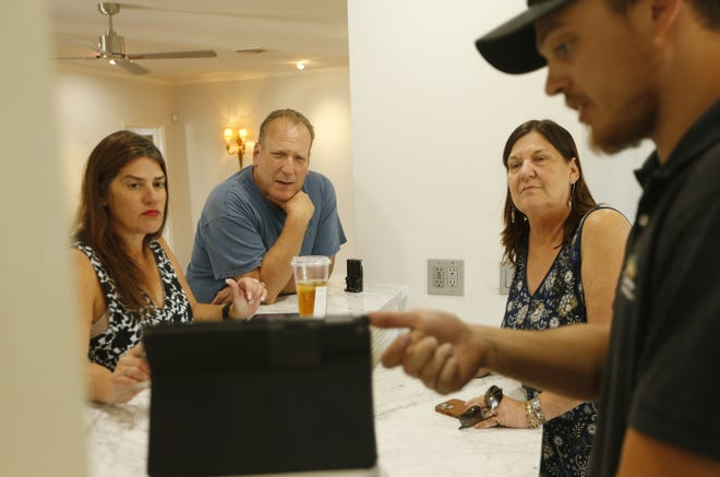 Inspector Jake Larson, right, goes over some of the potential issues with agent Christa Lawcock, left, and her clients, Mike and Lynne Sherman, in the historic Encanto neighborhood in Phoenix on May 21, 2021.