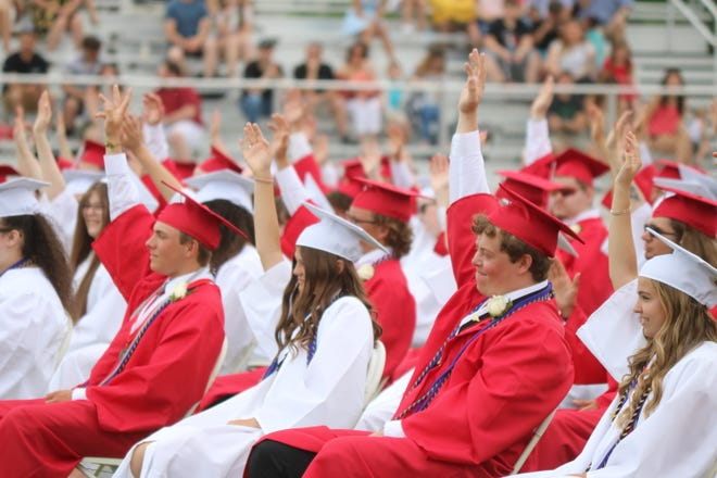 Port Clinton High School's Class of 2021 raise their hands as high as they possibly can, symbolizing their efforts to reach the edge, during the 137th annual commencement ceremony held in True Lay Stadium on Saturday.