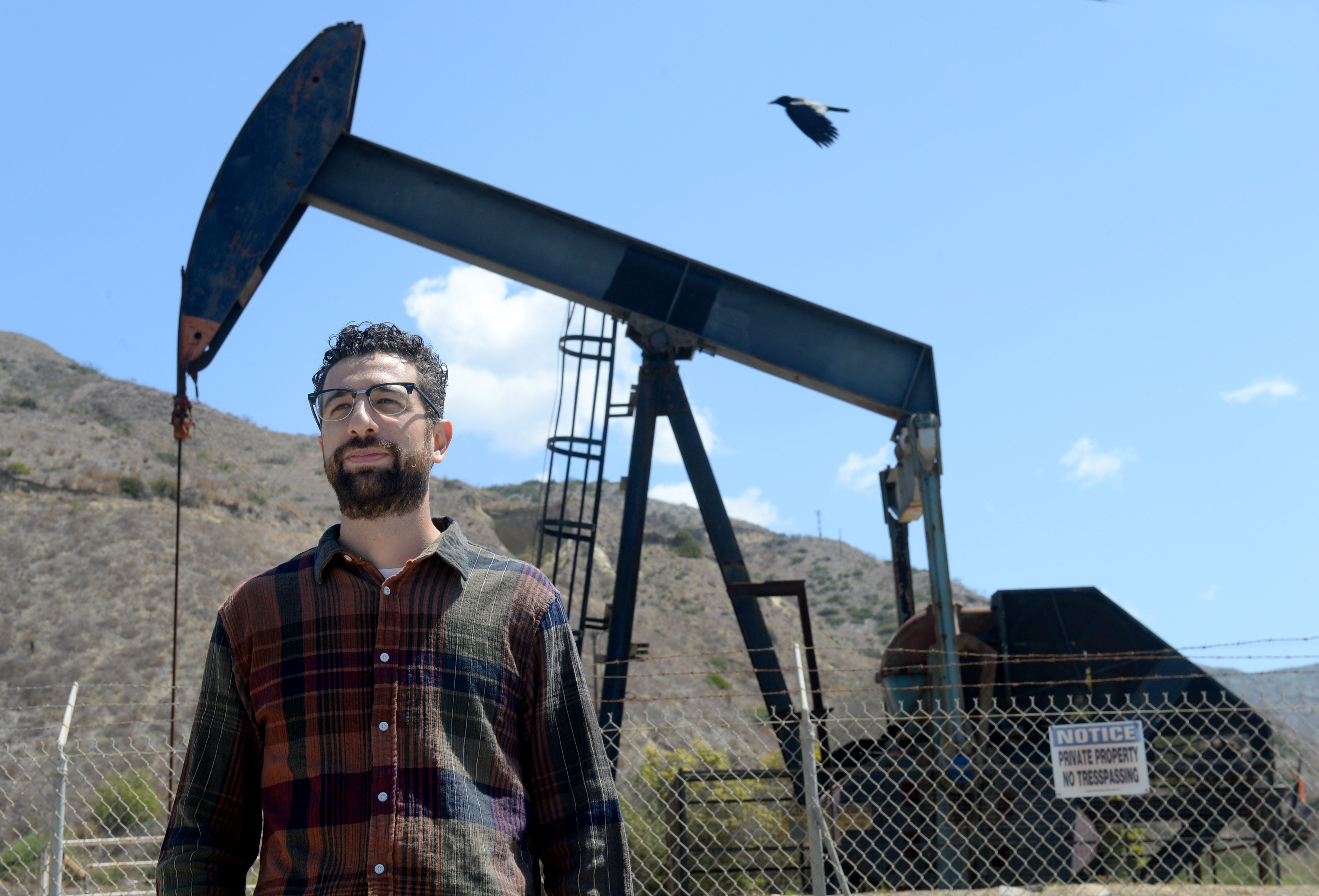 Tomas Rebecchi, an organizer with environmental group Food and Water Watch, stands near an oil well owned by California Resources Corporation along the Central Coast.