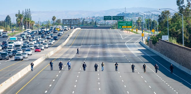 Police investigators walk along the closed northbound lanes of the 55 freeway south of Chapman Avenue looking for evidence after a shooting May 21 in Orange, Calif. A 6-year-old boy seated in the backseat of his mother's car was shot to death by another motorist, authorities said.