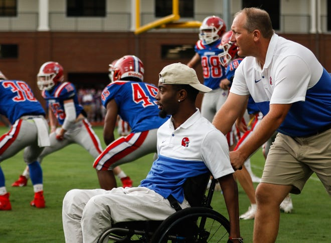 Jefferson assistant football coach Devon Gales makes his way onto the field before the start of a GHSA high school football game. Gales will resume his college career this fall at UGA.