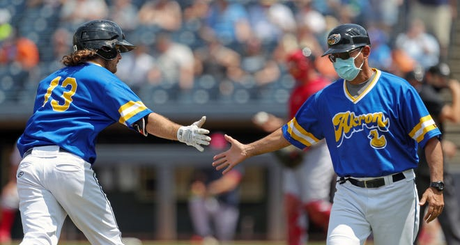 Akron RubberDucks manager Rouglas Odor, right, congratulates Akron RubberDucks outfielder Trenton Brooks (13) as he rounds third after hitting a three-run homer during the first inning of a Minor League Baseball game at Canal Park, Sunday, May 23, 2021, in Akron, Ohio.