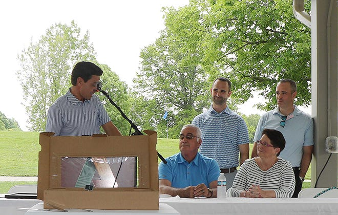 ASHLAND Mayor Matt Miller reads a city proclamation Saturday in honor of Dan Priest, front left, as from left in the back are Priest's sons, Kory and Kevin, and his wife Cindy during a ceremony to dedicate the Brookside Golf Course putting green in Priest's name. Ohio Sen. Mark Romanchuk also read a state proclamation to honor Priest, the Ashland High School boys golf coach and longtime golf pro who has been involved in the local junior golf program for many years. A fund for the junior golf program also has been created in Priest's name.