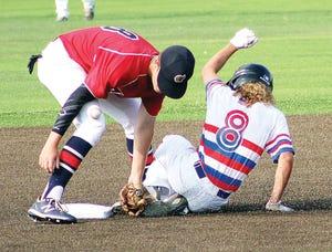 Nik Johnson, left, tries valiantly to make a play during American Legion Baseball action last summer. (Mike Tupa/Examiner-Enterprise)