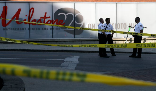 Crime scene tape surrounds Bicentennial Park Downtown on the morning of May 23 as Columbus police investigate a shooting from the night before that killed one and injured several others.