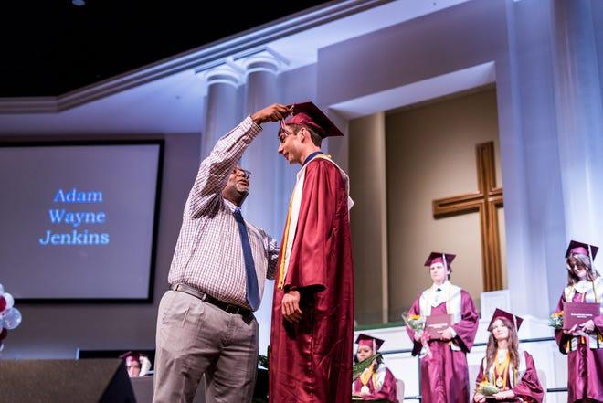 Vice Principal Troy Jackson moves Adam Jenkins' tassel during the awarding of diplomas Saturday at Covenant Christian School's graduation ceremony, held at First Baptist Church in Houma.