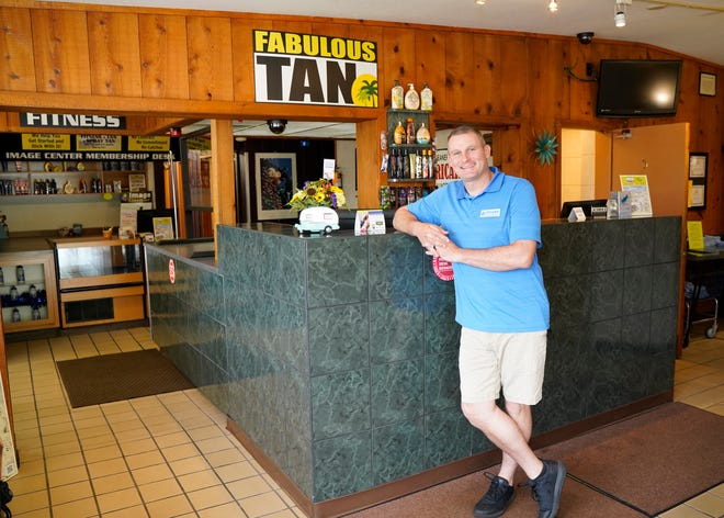 Darrin Morton, who with his wife, Alisha, recently bought The Adrian Image Center businesses on North Main Street, is pictured May 20 at the front desk.