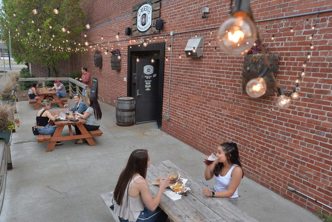 Madi Beining, 22, near left, and Lauren Leyson, 23, join others dining outdoors Saturday at Lavery Brewing in Erie.
