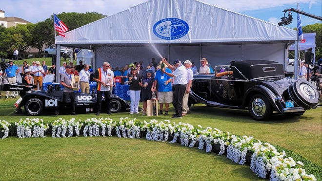 Amelia Island Concours d'Elegance founder/chairman Bill Warner sprays champagne (center) as a 1926 Hispano-Suiza H6B Cabriolet (right) and 1974 Shadow DN4 are crowned Best in Shows at Sunday's 26th annual event.