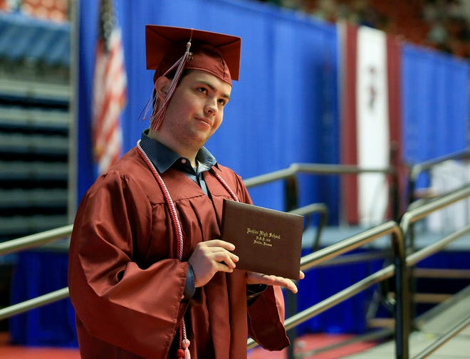 Blake Luman holds up his diploma cover for a photo as he graduates with the Buhler High School Class of 2021 Saturday morning at the Sports Arena.