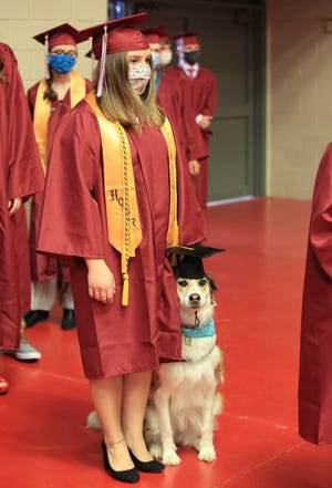 Katrina Calvert and her service dog Kadee wait to walk to their seats during the Class of 2021 Buhler High School graduation ceremony at the Sports Arena Saturday morning. Calvert later gave the Projections address to her fellow classmates with Kadee by her side on the stage.