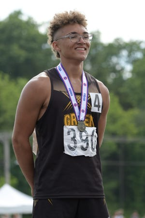 Green City's Asher Buggs-Tipton smiles while standing on the podium after winning the boys 110m hurdles race Saturday at the 2021 MSHSAA State Track Championships.