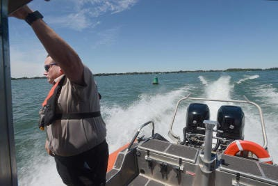 Reserve Deputy Jammie Francisco holds on as the Monroe County Sheriff's Office marine division patrols the waters of Lake Erie during the Summer of 2016.