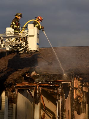 Firefighters house down the roof of an apartment in Dundee Sunday morning. The investigation has begun as to what started the fire that claimed the life of a tenant at the Village Pointe Apartments.