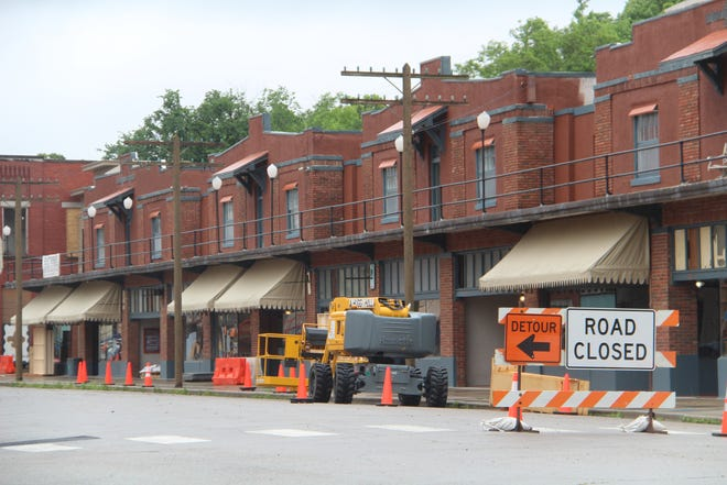 This image of Historic Whiting Hotel suites on the second floor and retail spaces on the ground floor shows some of the work done by movie set preparation crews. Awnings have been installed over retail spaces, and the fronts of the hotel suites on the second floor have been painted in a dark hue.