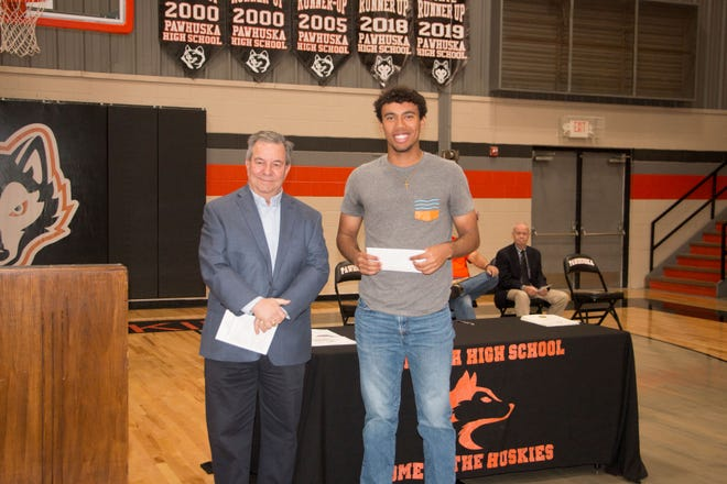 Isaiah Walker, at right, recently received the Blue Sky Bank Scholarship for $1,000 from Alan Brown, left, of Blue Sky Bank. Brown made the presentation during the annual Pawhuska High School awards assembly for juniors and seniors.