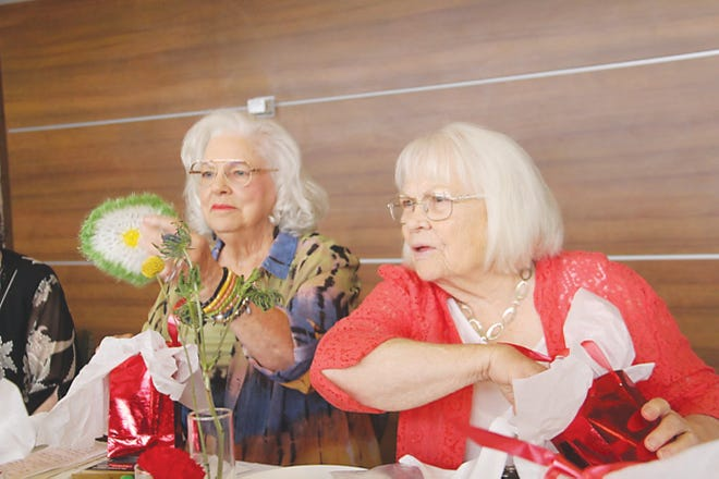 Myrna Clapp, president of the Barnsdall High School Class of 1956, and classmate Pat Gamble, right, examine items from their gift  bags before dinner last Thursday at the Copper Restaurant in the Price Tower in Bartlesville. The class held its 65th-year anniversary.