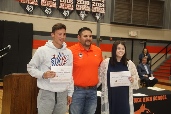 Danny Ferguson, center, of American Heritage Bank in Pawhuska recently presented two $500 Kevin Manering Scholarships to Pawhuska High School students during the annual awards assembly for juniors and seniors. The students were Samuel Tell Richardson, left, and Katauna Cochrane, right.