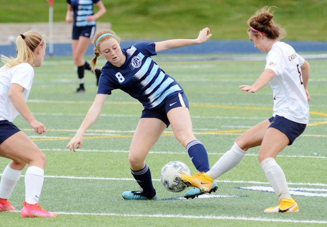 Petoskey's Anna Dundon fights for possession with a pair of Cadillac players during the first half.