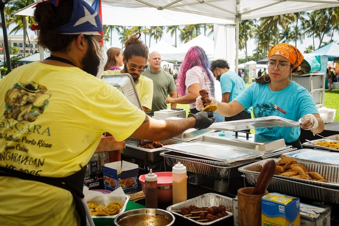 Staff at Bángara, a vegan pop-up restaurant based in Coconut Grove, work to fill orders at VegFest in downtown West Palm Beach on Sunday. Bángara creates authentic Puerto Rican vegan fare. THOMAS CORDY / PALM BEACH POST