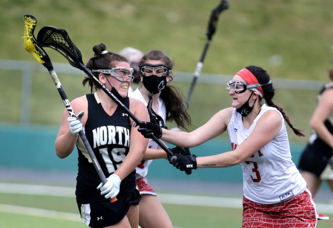 Cranston West and North Kingstown face off in a girls lacrosse match this season, a year after COVID-19 canceled the spring high school sports season.