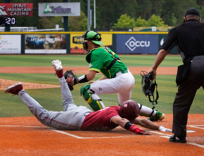 Stanford's Christian Robinson slides home for the score ahead of the throw to Oregon's Jack Scanlon during the sixth inning.