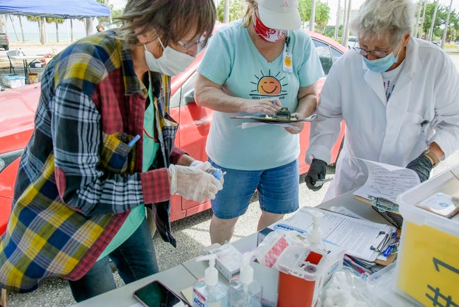DOH volunteers R.N. Peggy Lang and Karen Certalic work with Dr. Milena Henzlova in the COVID-19 vaccination line at the All Faiths Food Bank combination clinic and food distribution in May.